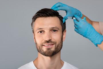 Handsome man having hair treatment at salon