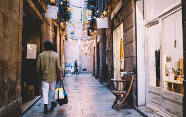 Back view of young trendy dressed hipster guy with bag walking in historical center in evening, rear view 20s of man recreating and strolling on narrow city streets on urban settings in dusk