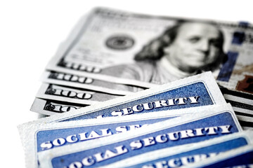 Social Security Cards in a Row Pile for Retirement With Cash Money