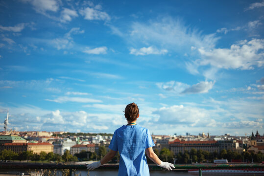 modern physician woman in scrubs outdoors in city against sky