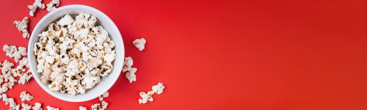 Bowl of popcorn on red background, top view