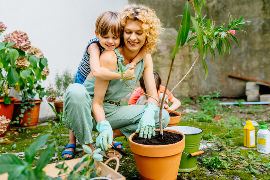 Cute child boy hugging his mother gardener at backyard garden. Happy lovely mom with children outdoor. Hobbies and leisure, home gardening, houseplant, urban jungle concept.