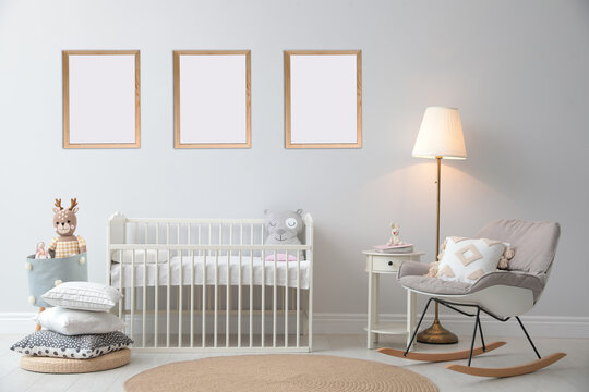 Stylish nursery interior with empty posters on wall. Mockup for design