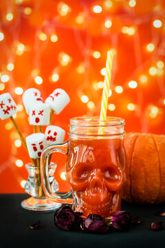 glass mug skull with red tomato juice. a welcome cocktail at a halloween party. marshmello scary faces, ghosts. pumpkin