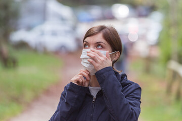 Flue and corona safety concept. Woman putting on face mask to protect herself, outdoors