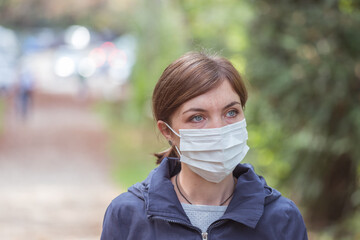 Flue and corona safety concept. Woman wearing face mask to protect herself, outdoors