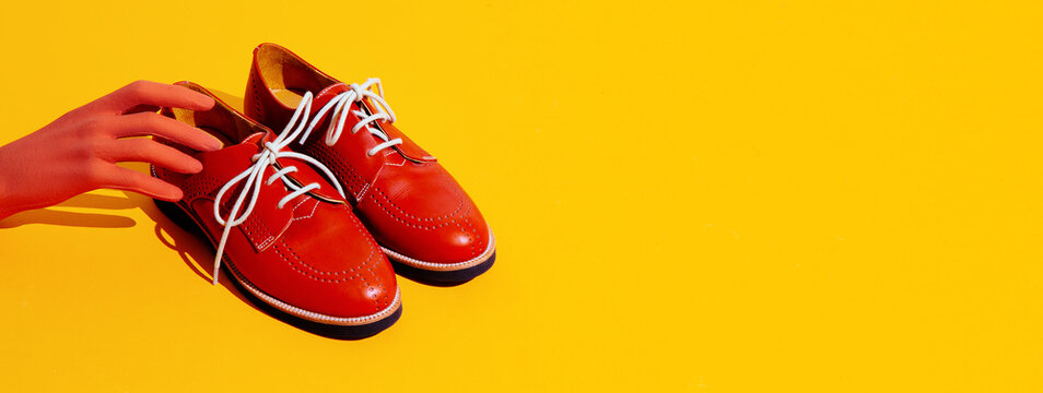 Fake hand and vintage shoes on yellow background. Fashion still life isometric minimal design
