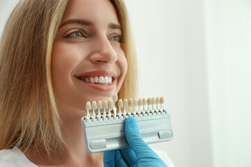 Doctor matching patient's teeth color with palette on light background, closeup. Cosmetic dentistry