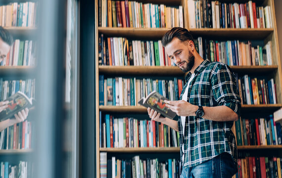 Smiling young man choosing magazine in bookstore