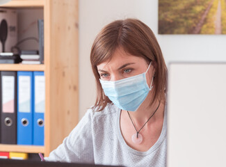 Protection in office in corona crisis: Woman with face mask is sitting on his workplace