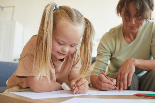 Portrait of cute blonde girl with down syndrome drawing with mother or teacher while enjoying development exercises