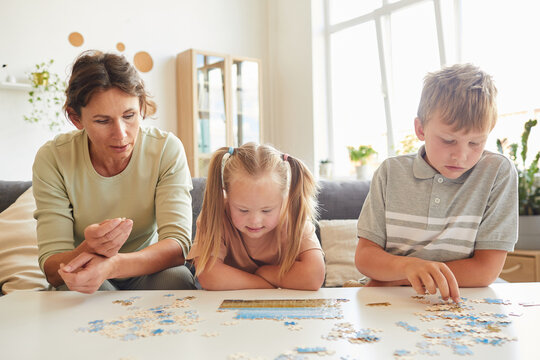 Front view portrait of loving family with special needs child playing with puzzles and board games together at home, copy space