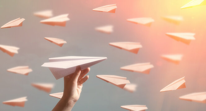 Paper plane flying in the opposite direction to other planes. Concept of individuality.