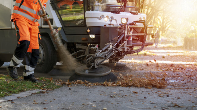 New generation of small electric street sweeper removing fallen leaves in body at autumn city park. Municipal urban services using ecology green vehicle lorry to clean streets from foliage.
