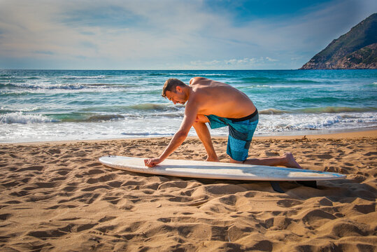 Man waxing a surfboard on the sand