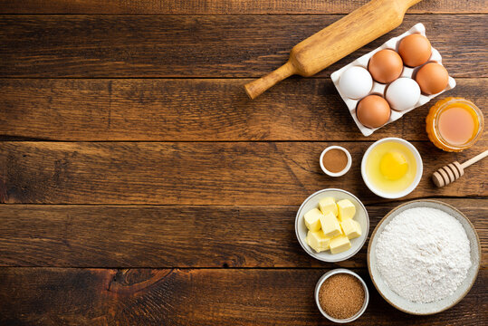 Cooking baking ingredients on a wooden table background. Flour eggs butter sugar and other pastry ingredients on wood. Top view copy space