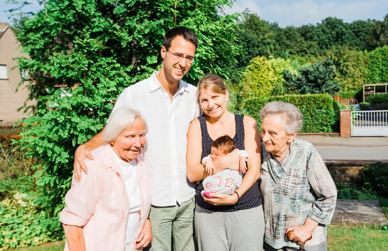 Happy multi-generational family with newborn baby outdoors
