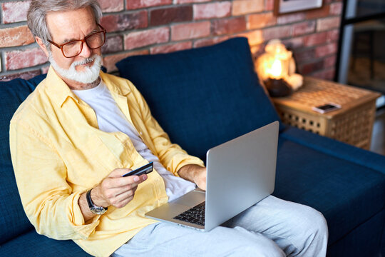 handsome senior male shopping online, use laptop at home. bearded man hold credit card in hands, going to buy smething online