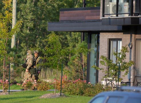 Special investigative unit members walk out of a condo building in Longueil