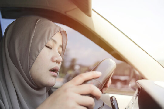 Female Asian muslim driver sleeping while driving a car, dangerous traffic safety accident crash car insurance
