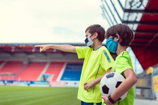 Two boys wanting to play football in stadium during covid-19