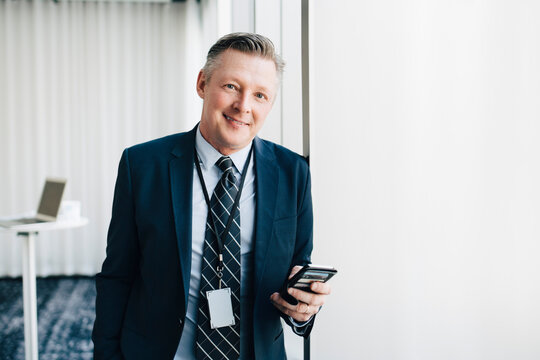 Portrait of smiling entrepreneur with mobile phone in office