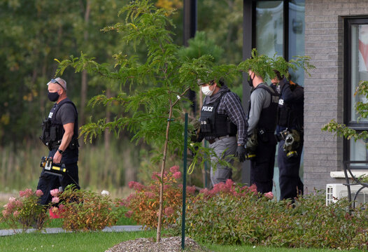 A group of police investigators walk out of  a condo building in Longueil