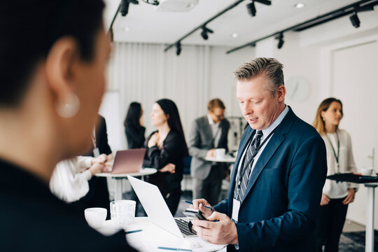 Businessman working over smart phone while standing in office seminar