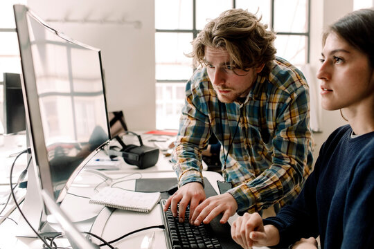 Businessman typing while coworker looking at computer in office