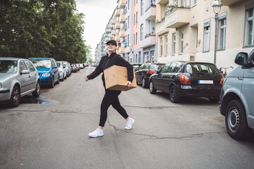 Confident delivery woman with cardboard box walking on street in city