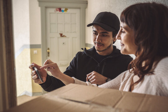 Female customer signing on mobile phone during package delivery
