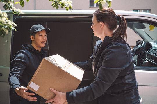 Side view of delivery woman giving package to coworker outside truck