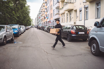 Confident delivery man with cardboard box walking on street in city