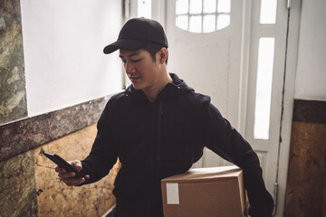 Delivery man using mobile phone while holding package against door