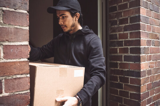 Delivery man with package standing in doorway