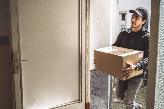 Confident delivery man with package standing at doorstep