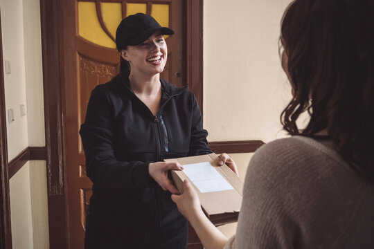 Smiling delivery woman delivering package to customer at doorstep