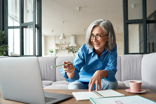 Happy mature older woman video calling on laptop working from home. Smiling 60s middle aged businesswoman talking by conference online virtual chat using computer at home office sitting on couch.