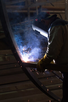 The welder is welding to structure steel material with gas metal arc welding process in the workshop.