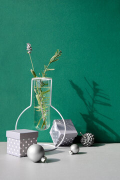 Christmas still life, minimal arrangement with winter flowers in modern glass vase and white Xmas decor.