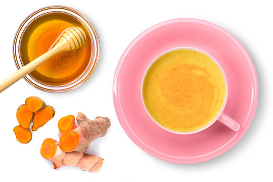 Cup of turmeric latte milk or golden tumeric tea with kurkuma root and pure honey isolated on white background. Top view. Flat lay.
