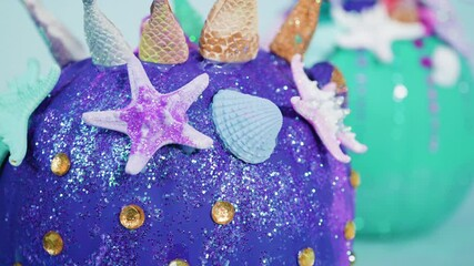 Wall Mural - Halloween craft pumpkins decorated with mermaid tails, glitter, and sparkly rhinestones on a white background.