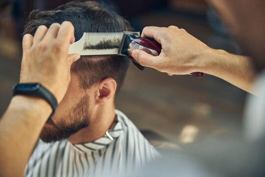 Skillful hair-stylist using electric hair clipper to cut hair