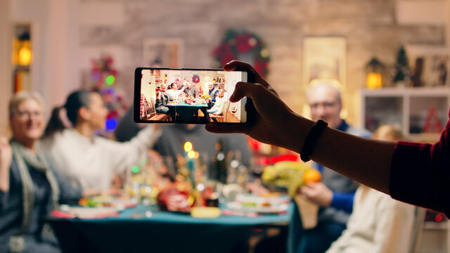 Girl taking a family portrait with her phones while celebrating christmas. Traditional festive christmas dinner in multigenerational family. Enjoying xmas meal feast in decorated room. Big family