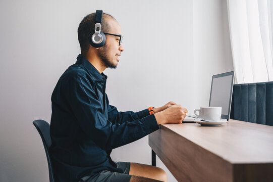 Young Asian businessman wearing shirt and casual shorts while online conference from home. Conceptual of working from home in covid-19 pandemic.