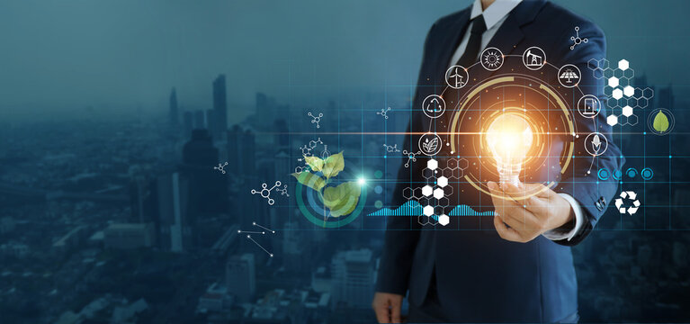 businessman holding light bulb against nature on city background  with icons energy sources for renewable, sustainable development,  Ecology and renewable energy concept.
