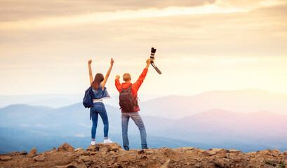 Happy travelers couple conquered top of mountain, raises hands up with camera and takes photos of landscapes on trip