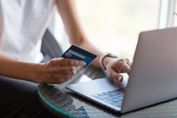 Young woman holding credit card and using laptop computer. Online shopping, e-commerce, internet banking, spending money, working from home concept