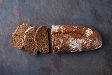Fototapeta Top view of sliced bread on dark background. obraz