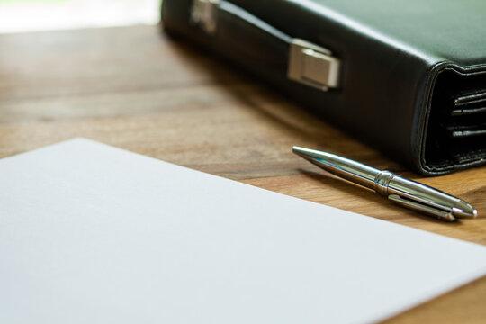 Aktentasche, Papier und Stift auf Schreibtisch